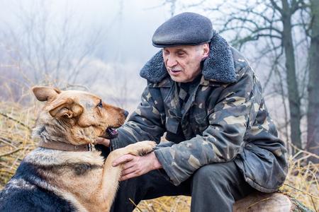 a man, a forester, sits on a stump, near him a dog, they communicate 版權商用圖片