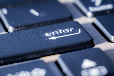 on the keyboard of the laptop - a close-up key to enter, a symbol for entering and storing information Stock Photo