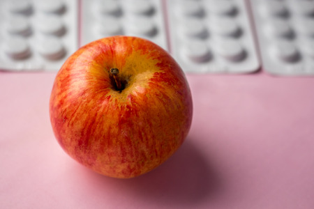 red apple on a tablets background, a natural product as an alternative to medicines Stock Photo