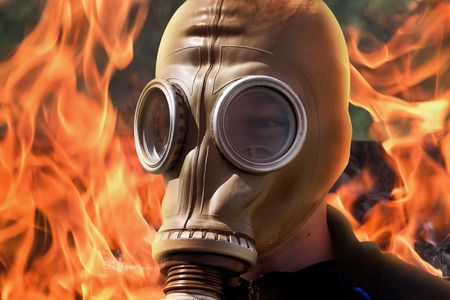 Man in  gas mask on  background of fire during  fire. Taming fire during an emergency Stock Photo