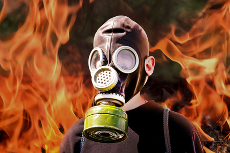 Man in  gas mask on  background of fire during  fire. Means of protection during fire