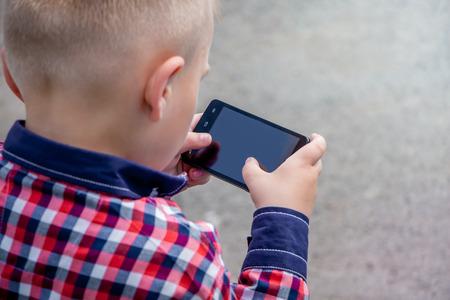 Piccolo ragazzo con uno smartphone nelle sue mani. Giochi per bambini preferiti sullo smartphone