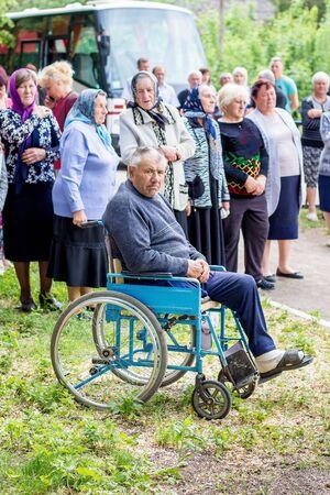 Ukraine. Khmelnitsky region. May 2018. Rally in  village in honor of  dead soldiers. Man on  wheelchair, surrounded by fellow villagers.  Ukrainian Village Standard-Bild - 143812578