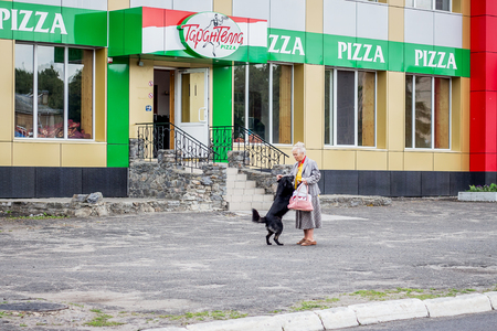 Ukraine. Khmelnytskyi. May 2018. An elderly woman hugging her beloved dog while walking through  streets of  city