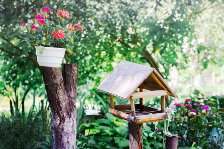 Feeder for birds in the garden near a flower pot. Summer sunny day in the park