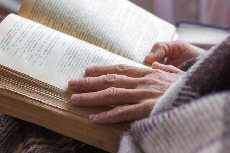 A woman reads a book. A woman holds a book in her hands. Bible reading and prayer alone