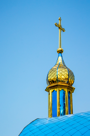 Golden dome of an orthodox temple against a blue sky on a sunny day