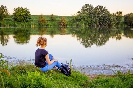 The girl sits on the bank of the river and contemplates the beauty of nature. Lonely with nature
