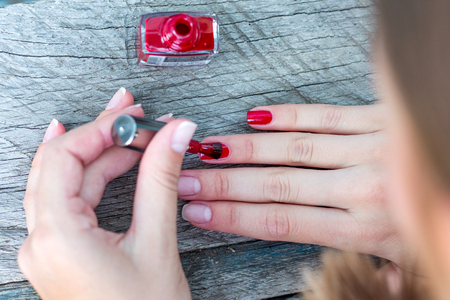 Causing of red varnish on the nail, manicure