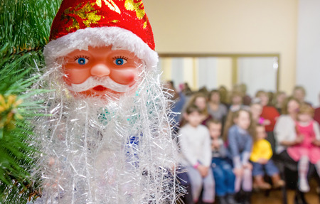 Mask Santa Claus on the Christmas tree during the New Years holidays in the hall with the children Stock Photo
