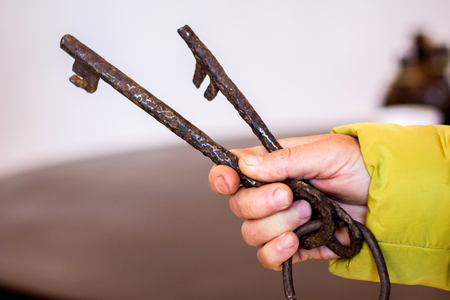 Old metal rusty keys in a woman's hand