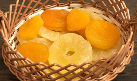 Dried apricots and dried pineapple in a wicker basket Reklamní fotografie - 151104898