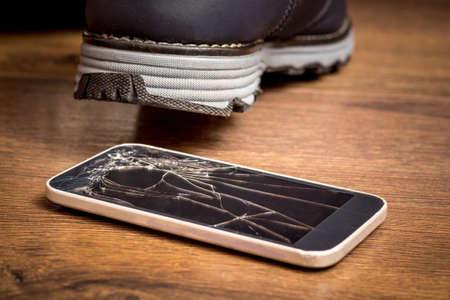 The man stepped on a cell phone and damaged the glass. A broken mobile phone needs to be repaired