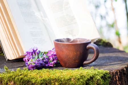 A cup of hot coffee in the woods on a stump next to an open book. Rest in the forest. Reading books in the woods in the wild