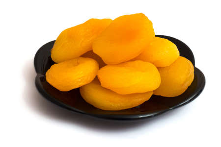 Dried apricots on a black plate, image on a white isolated background