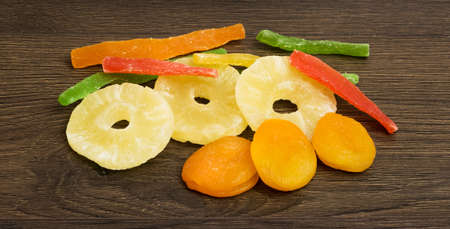 Assorted dried fruits. Slices of pineapple, dried apricots, candied fruits on a dark wooden background