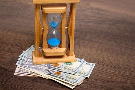 Sand Clock on dollar bills. Economy of time, time - money