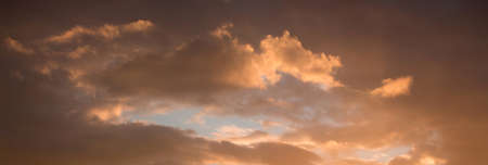 Dramatic clouds during the sunset. Through the dark clouds there is a blue sky visible. Panorama Foto de archivo