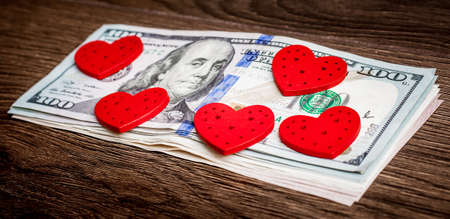 The red hearts lie on the bundle of dollar bills. I love money