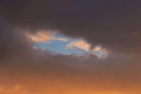 The sky is at sunset. Through the dark clouds can be seen a blue sky Foto de archivo