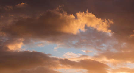 Dramatic clouds during the sunset. Through the dark clouds there is a blue sky visible