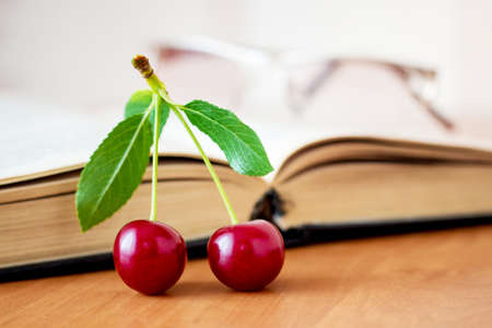 Two ripe cherries on the table near the opened book