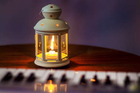Lantern with a candle on the table next to the piano in the room in the evening