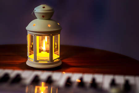 Lantern with a candle near the piano. Evening concert. Performing music in a romantic setting