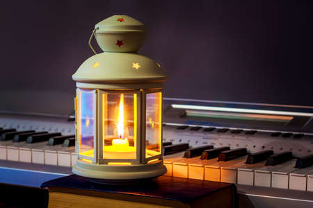 The lantern with a candle illuminates the keys to the piano. Music in an intimate setting Foto de archivo