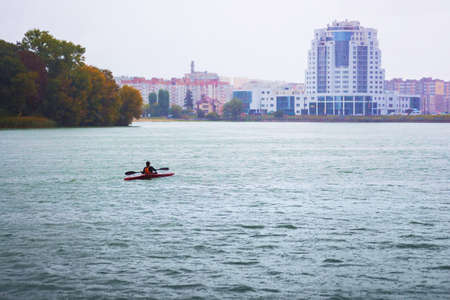 A man sailing on a boat (canoe) on a river in a rainy weather against the background of modern city buildings