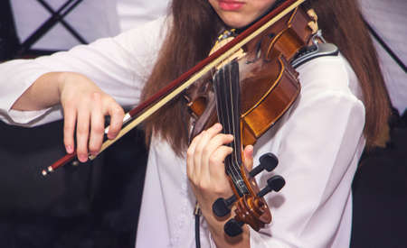 The girl plays the violin during the concert. Performing classical music