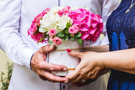 A man and women hold a bunch of flowers in their hands, greetings on the occasion of the feast
