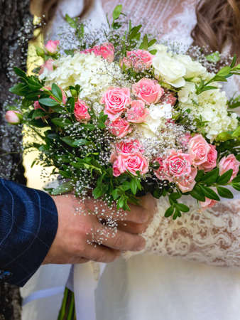 Bride and groom hold a bunch of delicate roses in their hands Stock fotó