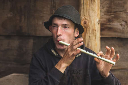 Ukraine, Yaremche. July 2019. Young guy from the mountainous terrain plays on a reed pipe, panpipe. Folk musician 新聞圖片
