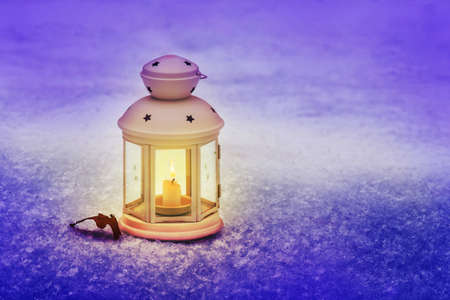 Lantern with candle on the snow on a winter Christmas evening. Celebrating New Year outdoors