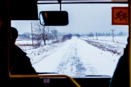 Winter road from bus window. Winter motor vehicle travel