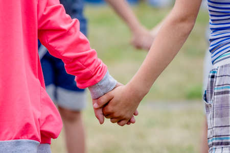 Boy and girl holding hands while playing. The concept of unity and trust