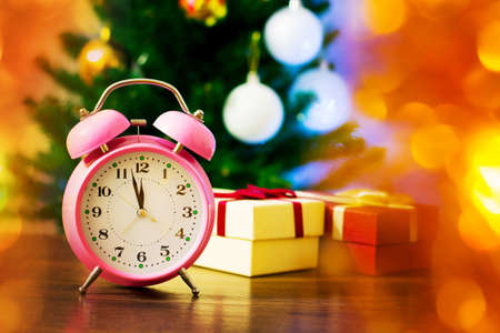 Clock against the background of Christmas tree and holiday gifts on New Year's Eve. The clock shows the approach of midnight before the new year 新聞圖片