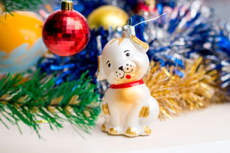 Toy dog near Christmas tree. Christmas toys. New Year greetings