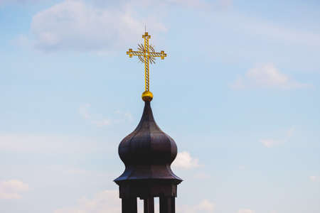 Cross on dome of orthodox church on sky background in sunny weather
