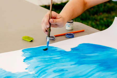 Girl performs drawing on paper blue paint. Girl holds a brush in her hand while drawing 版權商用圖片