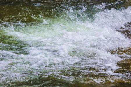 Waves in the mountain river. Fast flow of water 版權商用圖片