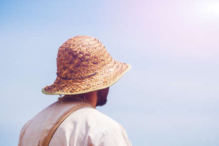Man in straw hat on sky background in sunlight Stock Photo