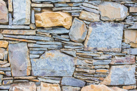 Background of masonry. Wall of different types of stone