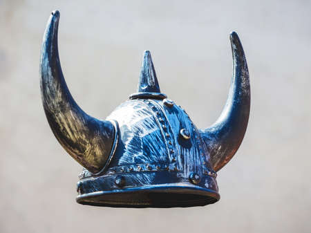 Helmet of medieval warrior on gray background, knightly helmet with horns