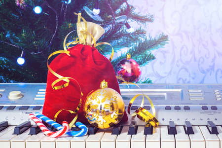 Christmas gifts near the piano. Music on New Year's night 新聞圖片