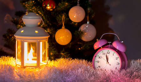 Clock and lantern with candle near Christmas tree at midnight. New Year's Eve. New Year and Christmas card