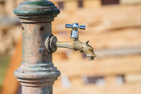 Old bronze water faucet outdoors in sunny weather, closed 版權商用圖片