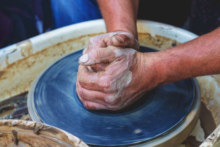 The potter forms a future product from a piece of clay on a potter's wheel. Potter's hands at work 版權商用圖片