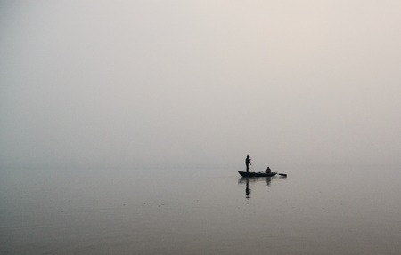 Fisherman in a boat on a foggy morning photo